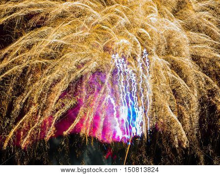 Golden sparkle with pink and blue. Spectacular fireworks  at a national fireworks championship at Belvoir Castle. Three of the UK best firework companies compete with a 10-minute firework display.