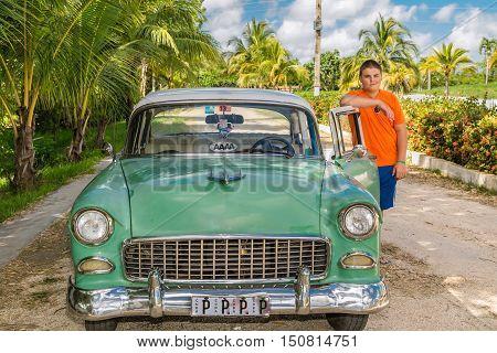 Cayo Coco island, village, Cuba, July 23, 2013, Teenage boy standing beside retro classic vintage car in tropical garden on sunny beautiful day