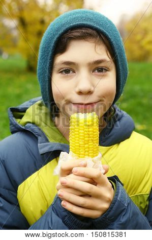 close up photo of kids mouth and boiled gold corn on the summer green outdoor background