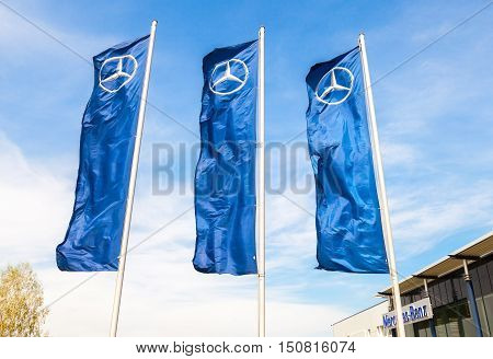 TOGLIATTI RUSSIA - MAY 3 2015: Dealership flags of Mercedes-Benz over blue sky near the office of official dealer. Mercedes-Benz is a German automobile manufacturer