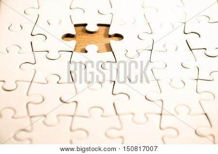 white jigsaw/puzzle whit one gap over a wooden table symbol of problem solving