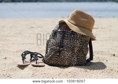 beautiful bag straw hat sandals on the golden sand summer day water