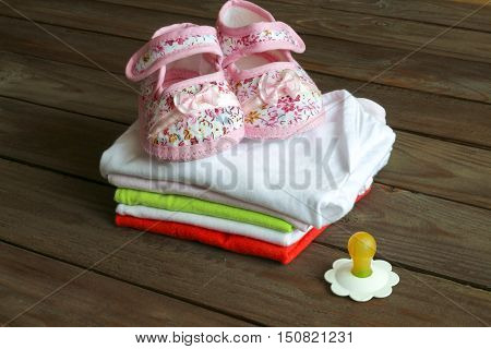 Kit for newborns. Baby clothes, booties on wooden background .