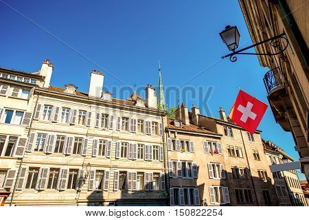 Buildings in the old town with Swiss flag in Geneva city in Switzerland