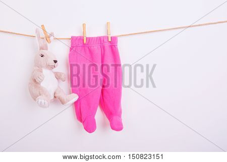 Baby goods hanging on the clothesline, white background