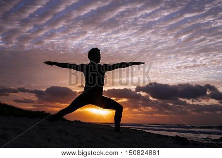 Man practice yoga at sunrise at the beach. (Pose: Warrior II, Virabhadrasana II)