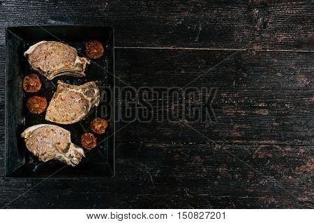 Porkchop baked on metal tray with tomato garnish