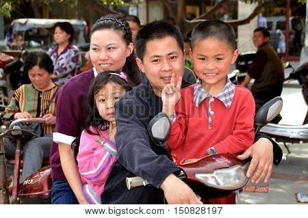 Pengzhou China - March 19 2010: Chunese man and wife riding on the family motorcycle accompanied by their two chlldren