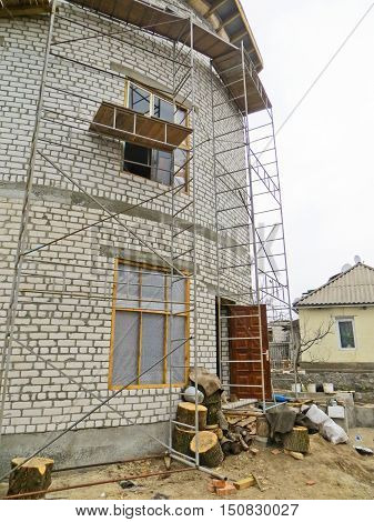 Building under scaffolding. Construction of the house