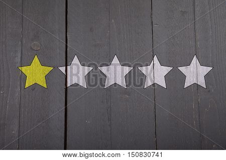 One yellow ranking star on black wooden background