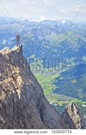 Young business man on top of huge mountain