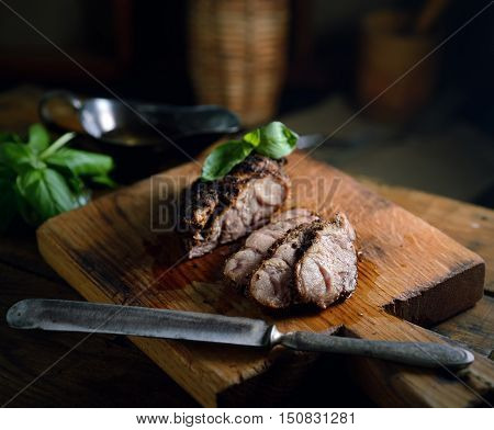 grilled meat, basil, vintage knife on a cutting board on a wooden background