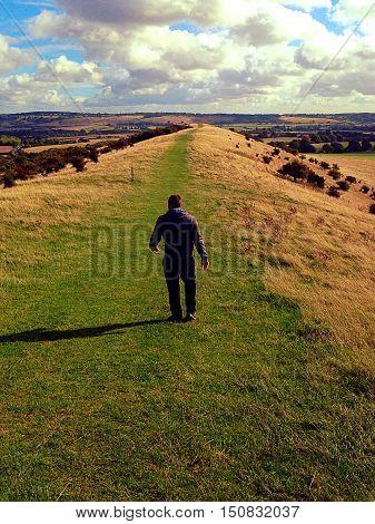 lone man walking on rolling hillside top