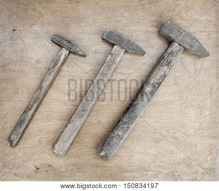 Old steel hammers with wooden handle on the wooden boards background