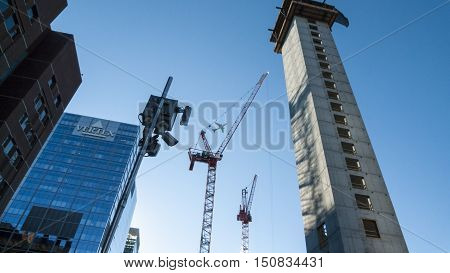 South Boston Massachusetts USA - September 24 2015: Jet climbing out of Logan Airport passes over One Seaport Square construction in South Boston