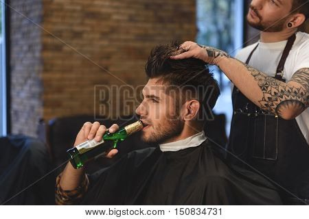 handsome bearded man relaxing with bottle of beer while hairstylist working