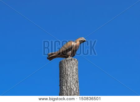 Figurine Of A Falcon On A Stump Of A Tree Against The Blue Sky. Figures Of Animals Made Of Wood. Woo