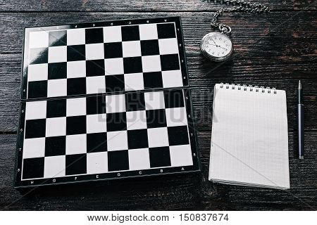 Empty chess board, pocket watch, note pad and pen on the table. Flat lay