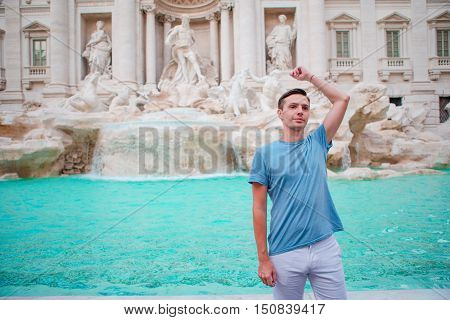 Young man near fountain Fontana di Trevi with coins in hands
