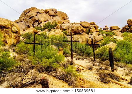Three Crosses on a Hillside in a Desert landscape with Boulders and Saguaro Cacti near the town of Carefree in Arizona, United States of America