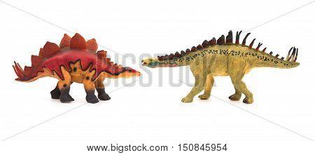 yellow huayangosaurus and red stegosaurus toys on a white background