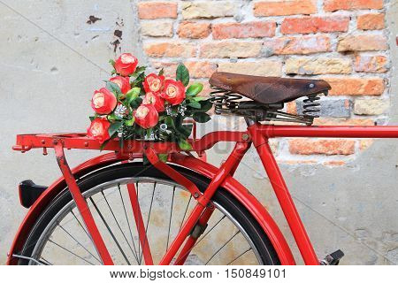 Closeup flower on saddle red bicycle classic vintage