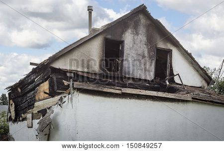 horizontal image of the top of an old white stucco house that has burned and is destroyed.