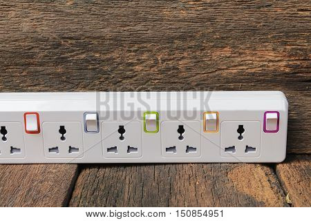 white plug socket electric power bar Closeup or extension block on wooden table background and copy space
