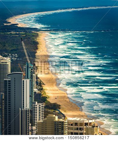 Aerial view from above of ocean sea beach and water waves with coastline buildings. Surfers Paradise Gold Coast Queensland Australia. Vertical