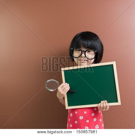 Asian School Kid Hold A Chalkboard And Magnifying Glass