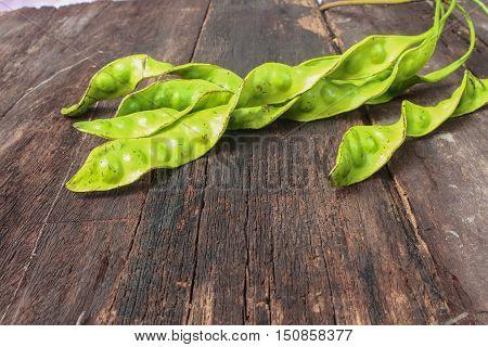 Parkia speciosa on wooden floor background ( bean petaitwisted clusterstink bittersato )