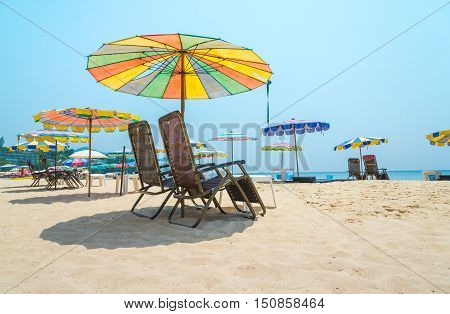 Lounger on white sand beach with blue sky background