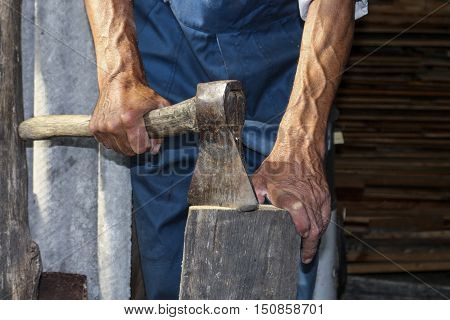 An elderly man with an ax chopping wood. Preparation for the winter period. Firewood.