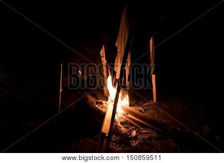 Dry clothes in camp fire in the night