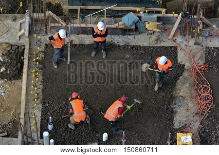 Construction Site Workers Leveling Cement In Building Site