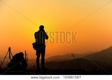 Silhouette of male traveler when he is taking photograph on mountain at sunrise.
