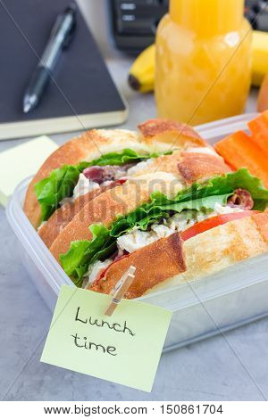 Lunch box with chicken salad sandwiches served with carrot sticks. Fruits and juice on workplace background vertical.
