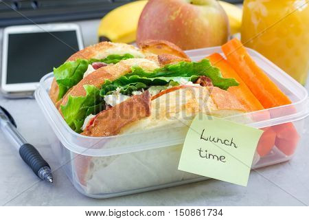 Lunch box with chicken salad sandwiches served with carrot sticks. Fruits and juice on workplace background horizontal