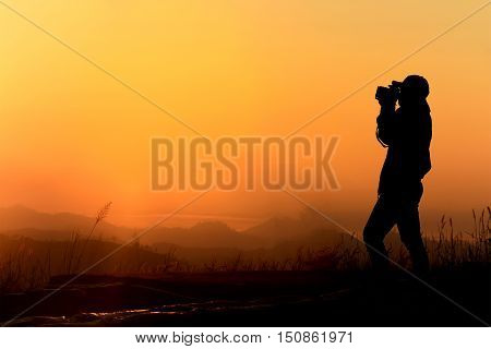 Silhouette of women is taking some photograph on mountain at sunrise.