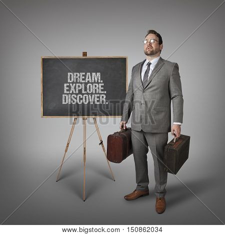 Dream. Explore. Discover text on  blackboard with businessman carrying suitcases