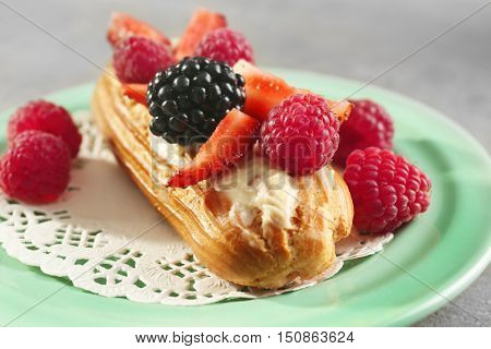 Green plate with delicious eclair, berries and doily, close up