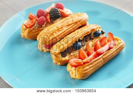 Delicious eclairs with berries on plate