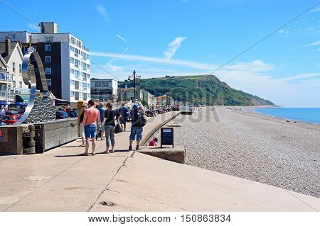SEATON, UNITED KINGDOM - JULY 18, 2016 - View of the pebble beach and promenade with holidaymakers enjoying the setting Seaton Devon England UK Western Europe, July 18, 2016.