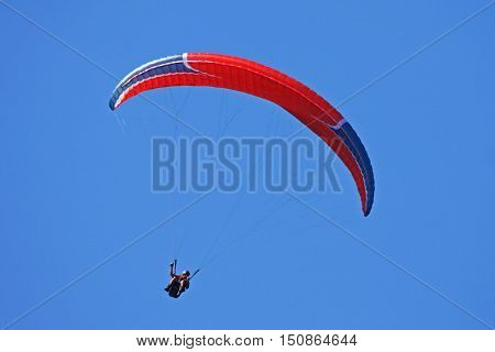 Paraglider under his wing in a blue sky