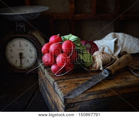 radish bunch, knife, apples, garlic on a wooden crate, vintage scales on a dark background