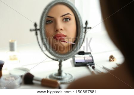 Beautiful young woman looking in mirror while applying makeup