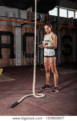 Girl getting ready for the rope climb exercise in gym