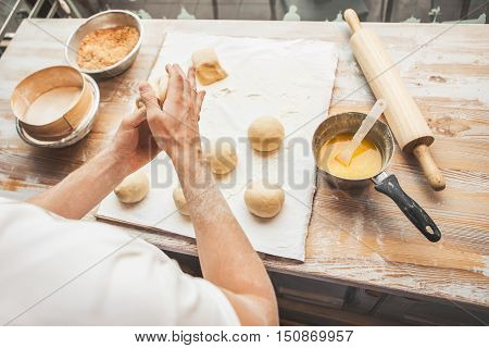 Making dough by male hands at bakery. Ingredients for cooking flour products or dough (bread muffins pie pizza dough).