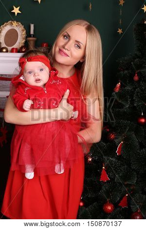 tender photo of beautiful mother with luxurious blond hair posing with her cute little baby girl beside Christmas tree in cozy home
