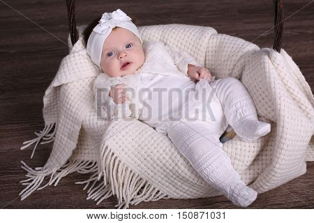 tender photo of small cute baby girl in cozy clothes laying on plaid